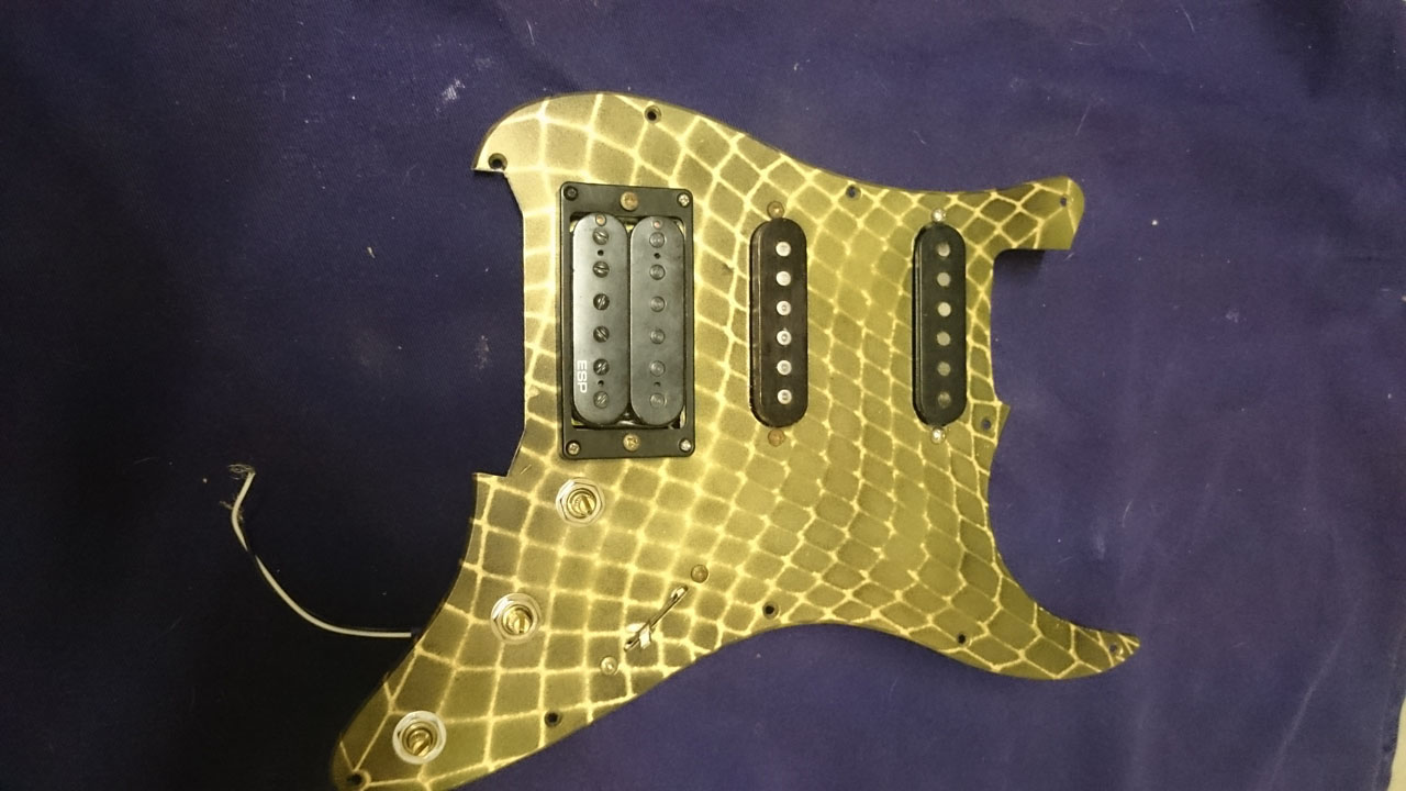 Turn your pickguard over and mount the hardware. Solder your input jack and  spring-claw wires — it's ready to screw into place.